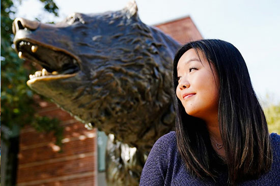 Student in front of Bruin statue